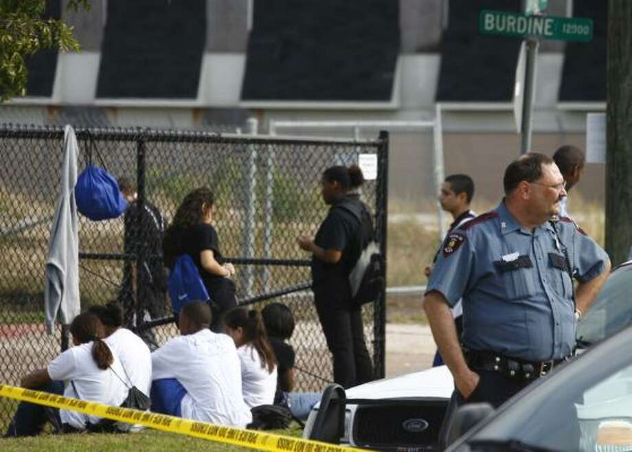 Students sit near the scene where a 16-year-old male Westbury High School student was shot and killed Tuesday morning in a drive-by shooting. Photo: Steve Ueckert, Chronicle