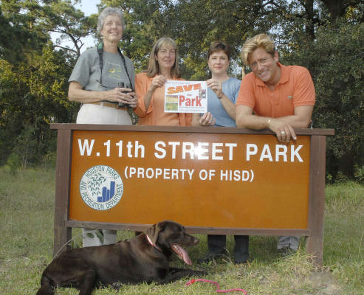 Area residents who want to save the West 11th Street Park include, from left, Peggy Boston, Nancy Greig, Pam Efferson and Brian Teichman, whose dog, Bertie, rests in front of the sign.