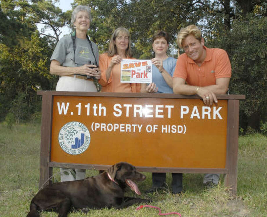 Area residents who want to save the West 11th Street Park include, from left, Peggy Boston, Nancy Greig, Pam Efferson and Brian Teichman, whose dog, Bertie, rests in front of the sign. Photo: TIM JOHNSON, For The Chronicle