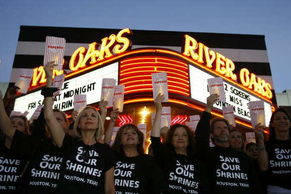 Members of the Save Our Shrines group gather for a publicity photo outside the River Oaks Theatre.