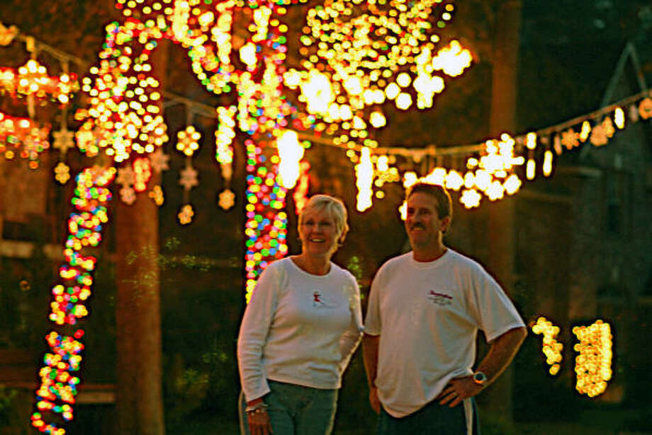 Neighbors Miki Holmes and Scott Alexander admire the holiday light display in the Panther Creek neighborhood of The Woodlands. Tangle Brush Drive neighbors use the lights to honor Cort Martin, a teenager who used to live on Tangle Brush Drive and died in an auto-train accident on FM 1488 in 2000, his senior year at The Woodlands High School. Photo: David Hopper, For The Chronicle