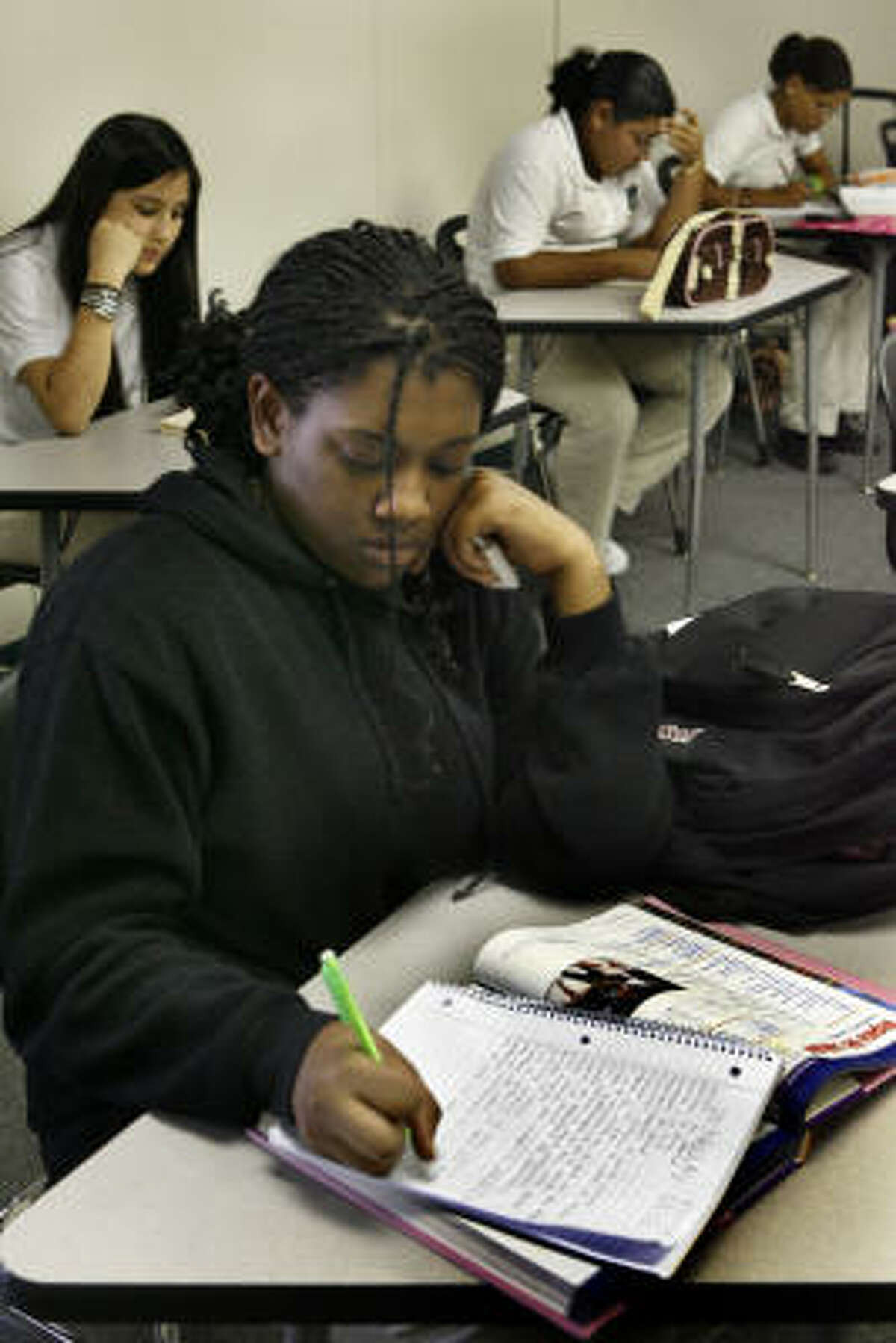 Nefertia Gilmore, 14, a ninth-grader, completes her homework. The program is a partnership of HISD, Houston Community College and the Asia Society, a New York nonprofit launching 10 such programs with funds from the Bill and Melinda Gates Foundation.