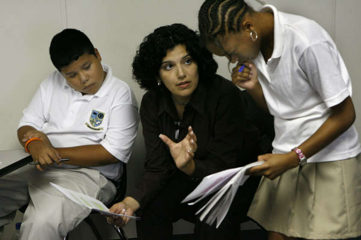 Alma Perez-Silva helps international program ninth-graders Juan Mendoza and Sydney Lamb, both 14, with their homework during study hall. About 100 HISD students have opted for the unique high school experience.