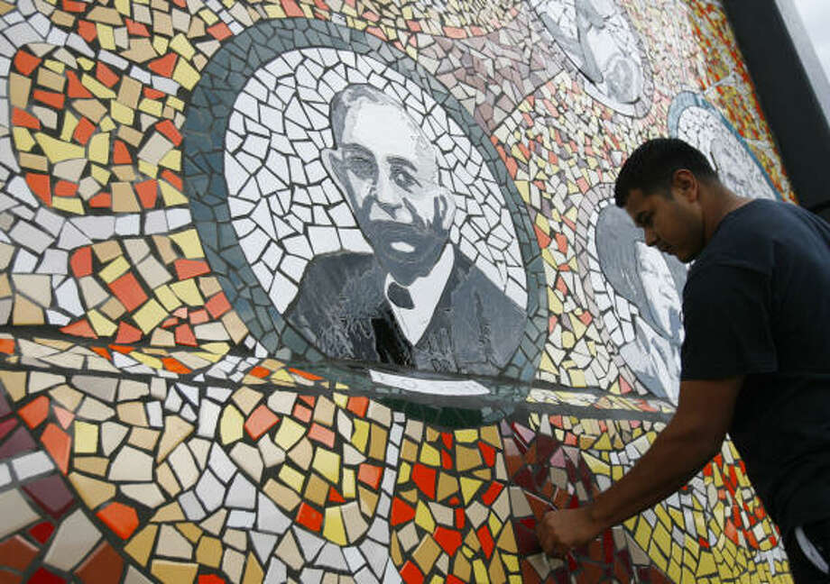 Israel Barbosa, with the Museum of Cultural Arts, Houston, scrapes glue from the mural drawn by Wheatley High School students. Photo: MELISSA PHILLIP, CHRONICLE