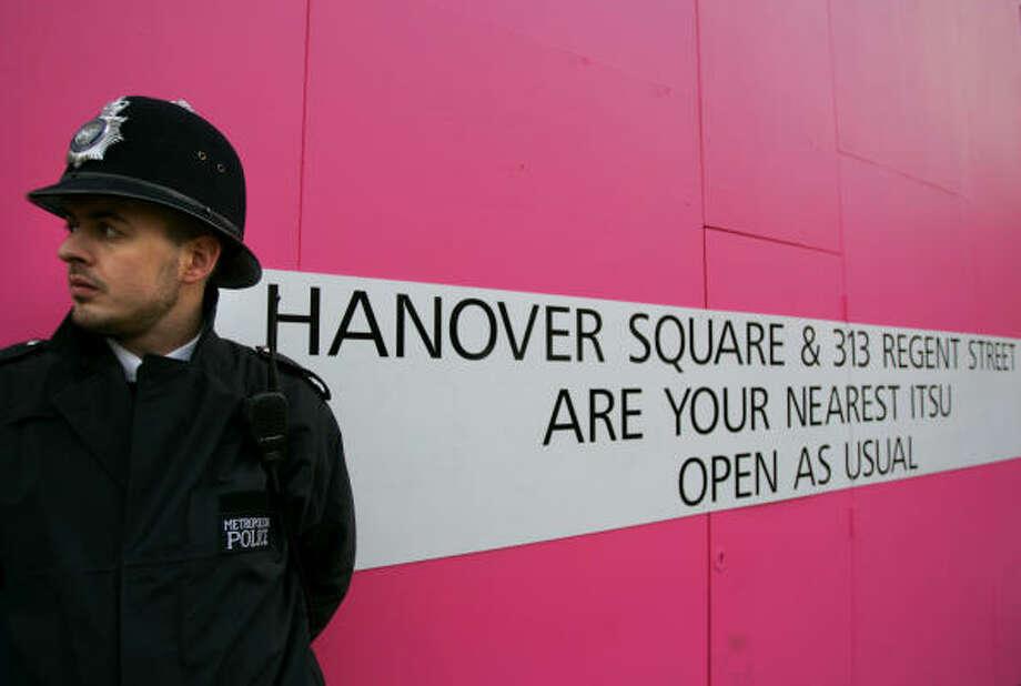 A British police officer Thursday guards a branch of Itsu su-shi restaurant in London, where the ex-Russian spy met a contact Nov. 1. Photo: MATT DUNHAM, AP
