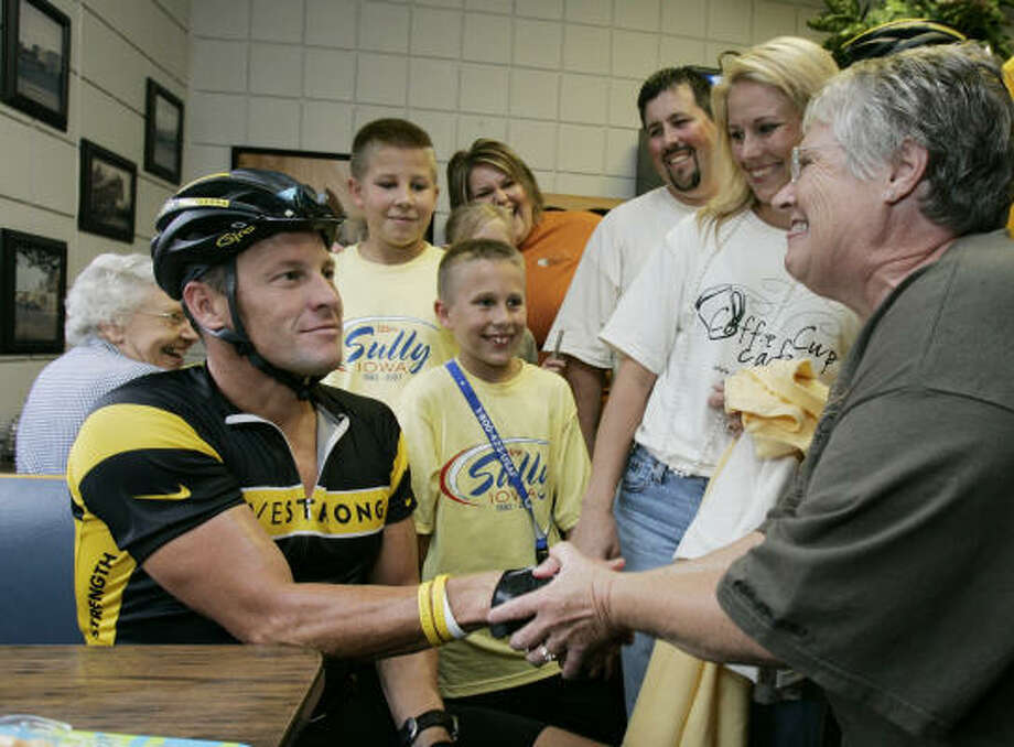 Seven-time Tour de France winner Lance Armstrong, left, greets well-wishers in a diner during a break from his seven-day bike ride across Iowa. Photo: CHARLIE NEIBERGALL, AP