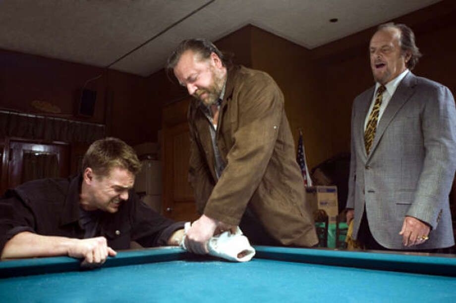 A mob boss (Jack Nicholson, right) has his henchman (Ray Winstone, center) smash a visitor's (Leonardo DiCaprio) arm cast to make sure he's not wearing a wire, in The Departed. Photo: Warner Bros.