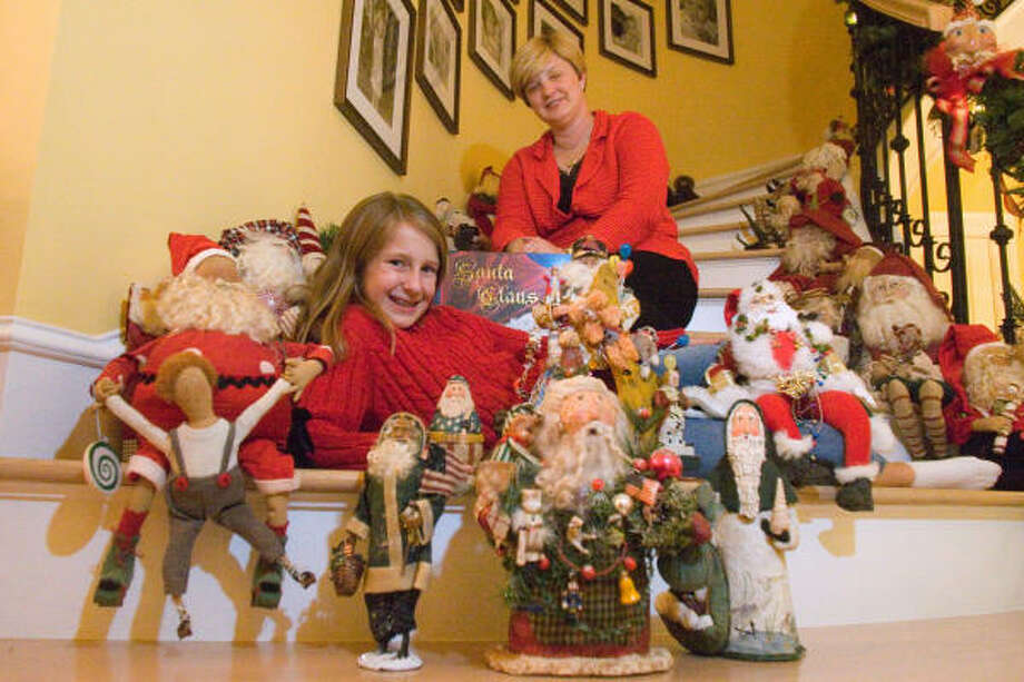 Kim Van Gundy and daughter Mattie, 11, show off a small selection of their 332 Santa figurines in their West University home. Photo: R. Clayton McKee, For The Chronicle