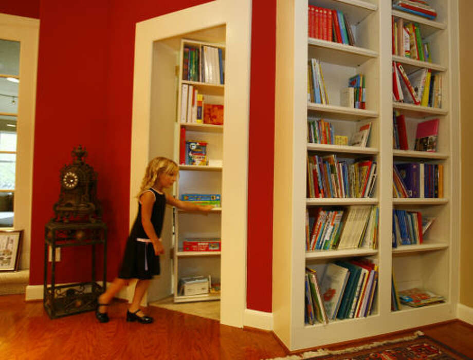 Madison Dillon, 4, walks through a door into her secret room used for home schooling. The door also serves as a bookshelf. Photo: Nick De La Torre, CHRONICLE