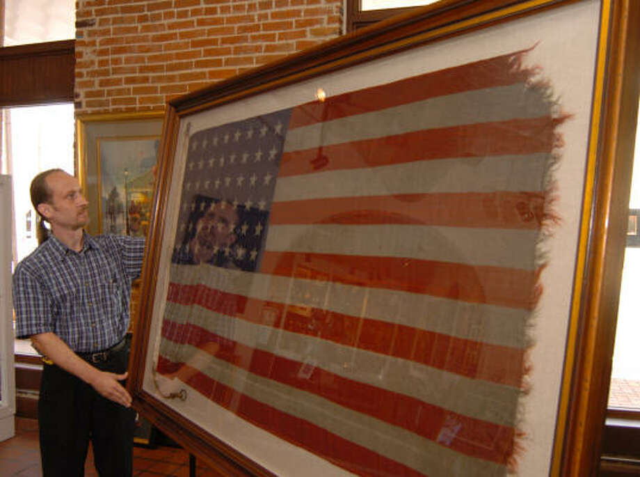 Woodlands resident David Woodard holds a framed American flag saved from a battle in World War II. The Certified Picture Framer works at Lampros Gallery in downtown Conroe. The flag belongs to Michael Seiler, Montgomery County assistant district attorney, whose grandfather Lt. Cmdr. William H. Seiler commanded Landing Craft Tank 271 during the D-Day invasion of Normandy. Photo: David Hopper, For The Chronicle