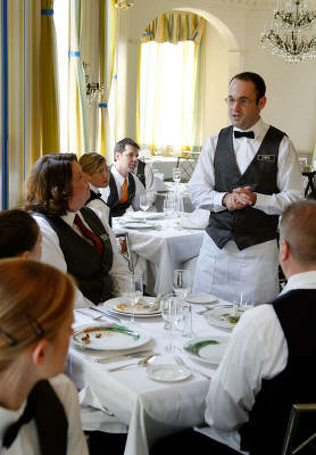 Commander's Palace waiter Chris Sander practices on other waiters in preparation for the reopening. Photo: ALEX BRANDON, AP