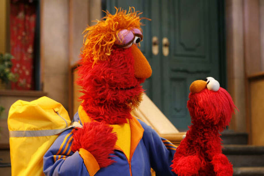 Elmo's father, left, explains to his son why he's leaving home in a scene from the Sesame Street special When Parents Are Deployed. Photo: RICHARD TERMINE, Associated Press