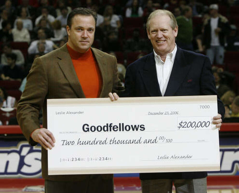 Houston Rockets CEO Tad Brown, left, presents Houston Chronicle Publisher and President Jack Sweeney with a $200,000 check for Goodfellows on Saturday during the Rockets game. Photo: Aaron M. Sprecher, For The Chronicle