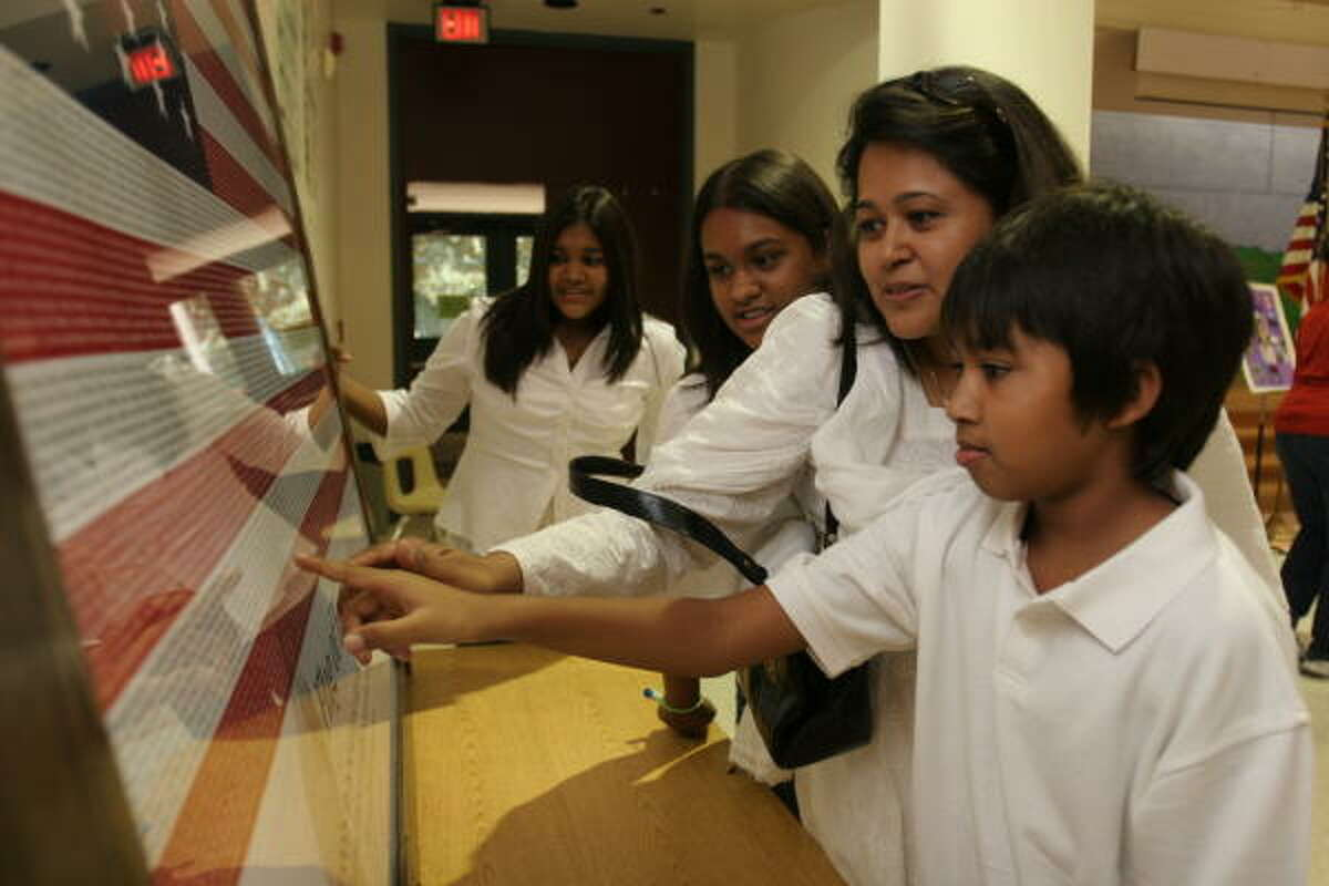 The family of Jayesh Shah, who was killed in the 9/11 terrorist attack on the World Trade Center, presented Katy Elementary School with an American flag bearing the names of all who were killed in the attack. Attending the event were Sonia Shah, 12, left, her sister Nikita, 14, their mom, Jyothi, and brother Kevin, 11.