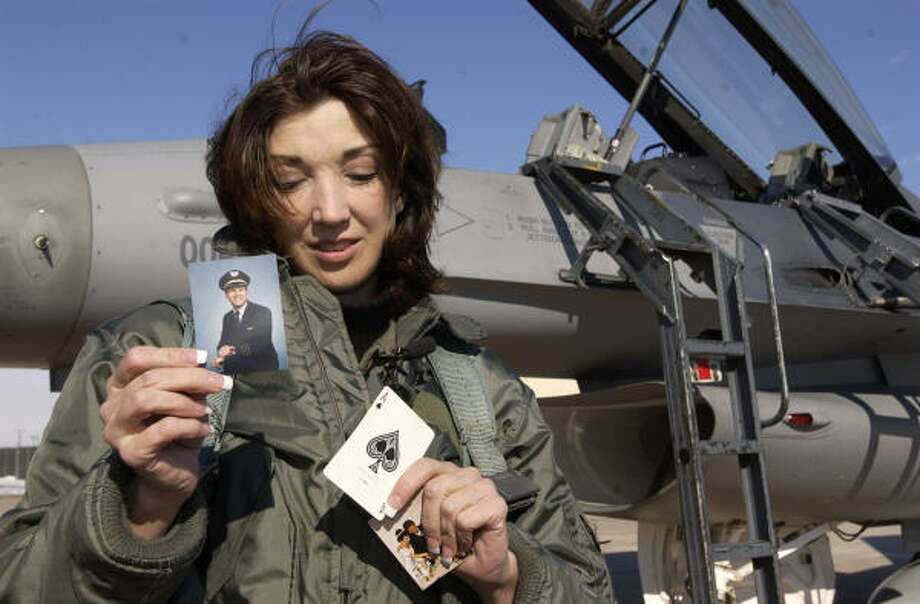 Sandra Dahl holds a photo of her husband, Jason, an ace card and their wedding photo after taking a ride on his behalf in an F-16 fighter jet in 2004 at Buckley Air Force Base, Colo. Now the widow has filed suit to have his remains moved from California to Colorado. Photo: JOHN LEYBA, AP