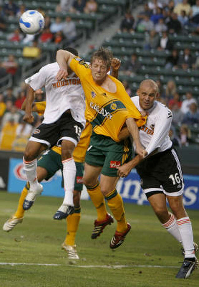 Los Angeles' John Wolyniec, center, gets physical with Dynamo defenders Craig Waibel, right, and Ricardo Clark in Carson, Calif. Photo: LUCAS JACKSON, ASSOCIATED PRESS