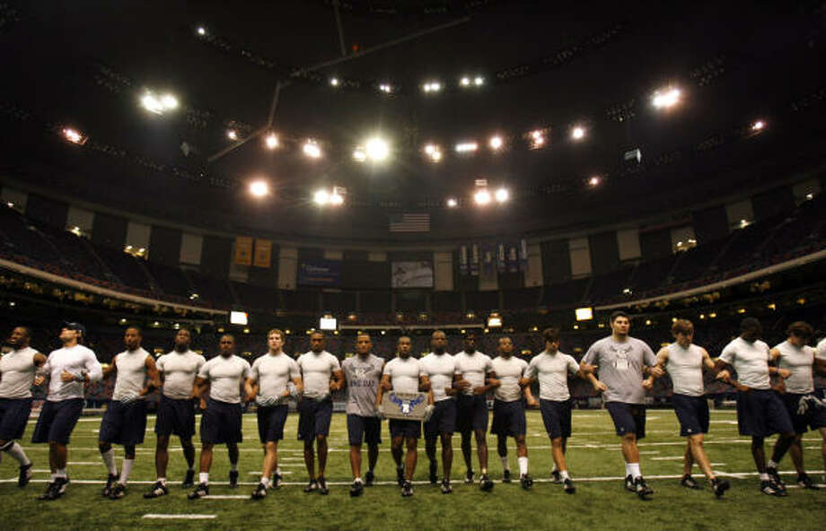 Rice players lock arms at the Louisiana Superdome during preparations for tonight's game against Troy. Photo: SHARON STEINMANN, HOUSTON CHRONICLE
