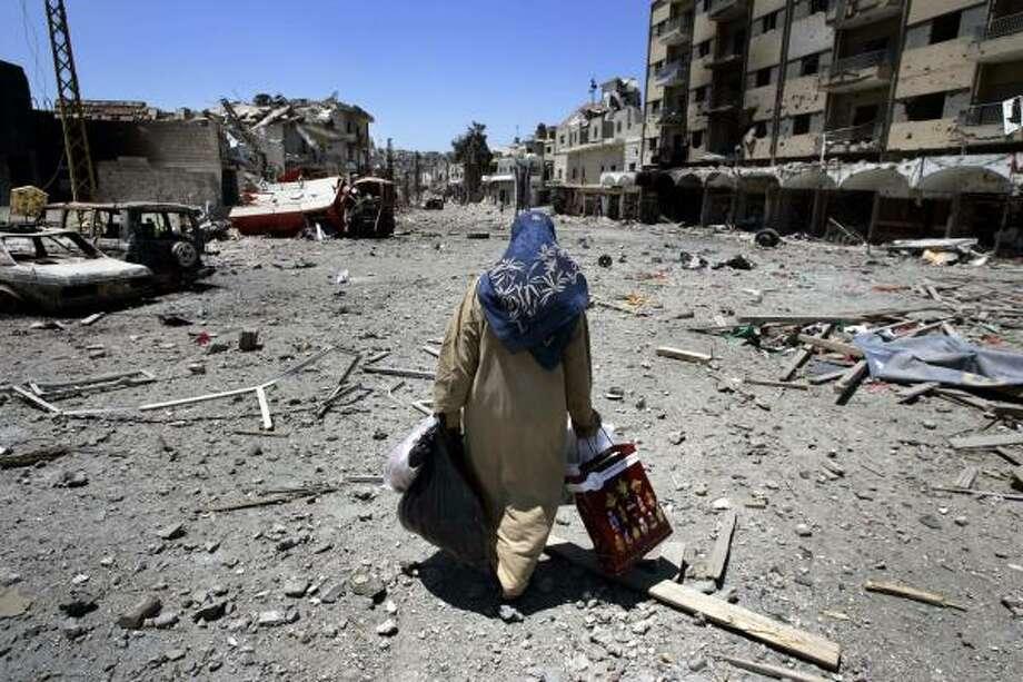 A Lebanese woman, carrying her belongings, flees the southern town of Bint Jbail, Lebanon. Photo: LEFTERIS PITARAKIS, AP