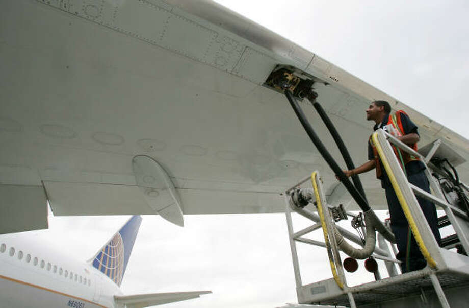 Kyle Smith of Allied Aviation Fueling Co. fills up a Continental Airlines Boeing 767. Falling oil prices could allow Continental and other carriers to post their annual profits in years. Photo: DAVID J. PHILLIP, AP File