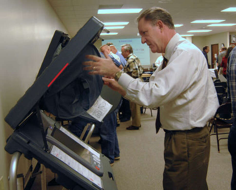 Rocky Alexander of Decker Prairie sets up the privacy shield on a voting machine. Photo: David Hopper, For The Chronicle