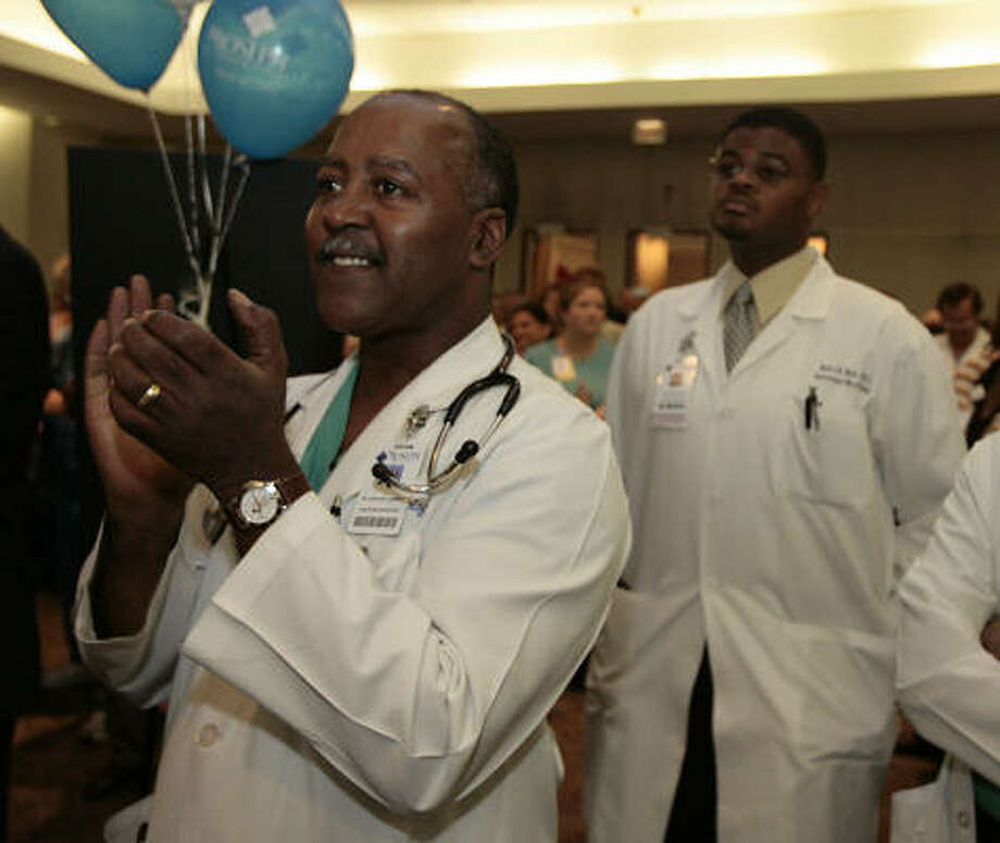 Drs. Garland Gossett and Eric Tait listen to the announcement that Hospital Partners of America completed its purchase of St. Joseph Hospital on Monday. Photo: Billy Smith II, Chronicle