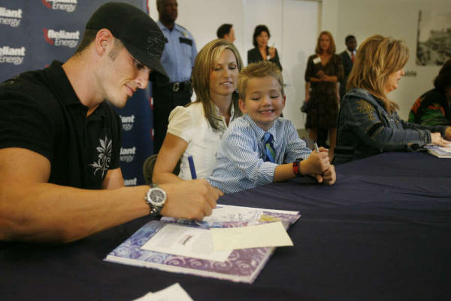 Texans quarterback David Carr, with wife Melody and son Austin, signs copies of Little Drop and the Healing Place at Reliant Plaza. Photo: Mayra Beltran, Chronicle