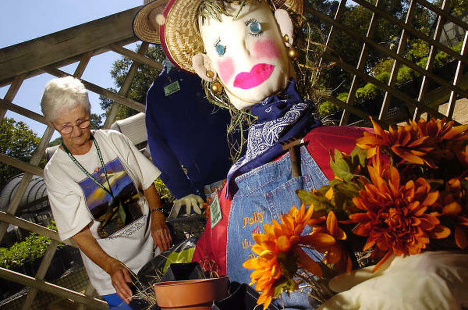 Volunteer Mary Ellen Brown works on a scarecrow at Mercer Arboretum. Photo: Dave Rossman, For The Chronicle