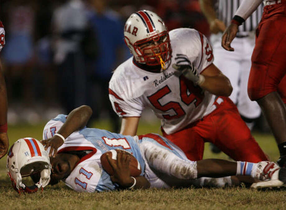 Madison High School sophomore quarterback Jeffery Lewis reaches out for his helmet after being hit by Lamar junior linebacker Steve Erzinger earlier this year. Erzinger and Lamar will try to do the same to Aldine on Saturday. Photo: Aaron M. Sprecher, For The Chronicle