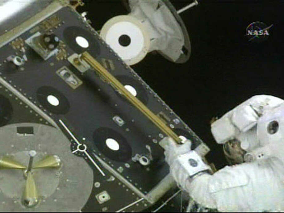 In this image made from NASA TV, astronaut Mike Fossum returns to secure his safety tether during a spacewalk. Photo: AP