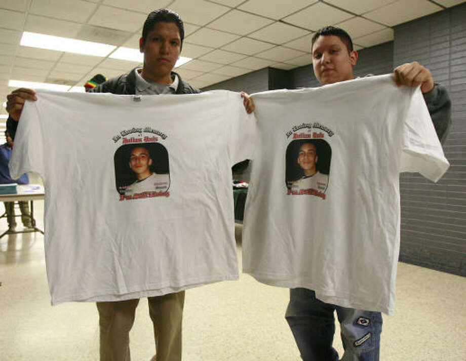 Brothers Asahelt, left, and Salathiel Olguin hold T-shirts that commemorate Julian Ruiz. The 16-year-old boy was killed last week in what police say was a gang-related drive-by shooting. Photo: James Nielsen, Chronicle