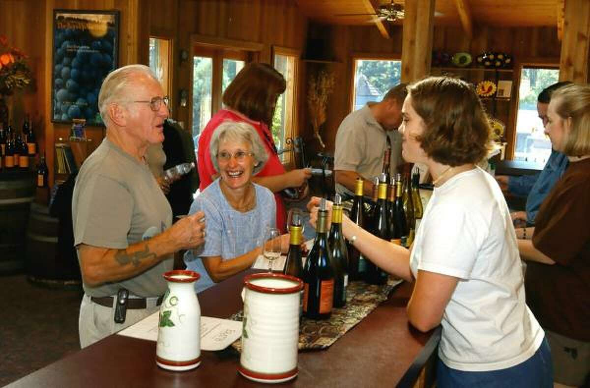 Visitors sample wines in the tasting room of Erath Vineyard in Dundee, Ore. But after the recent terrorist plot discovered in England, airline passengers can no longer carry on bottles of wine.