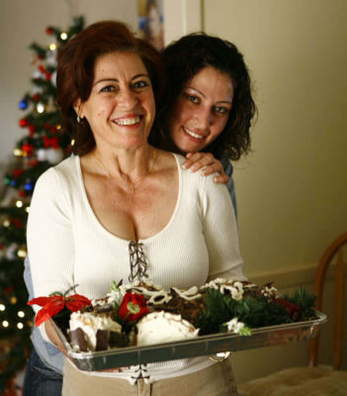 Mary'z Mediterranean Cuisine owner Mary Fakhoury, left, and daughter Mira enjoy decorating both home and dessert for the holidays. Bûche de Noël, a simple cake, is cut and decorated to resemble a tree trunk.