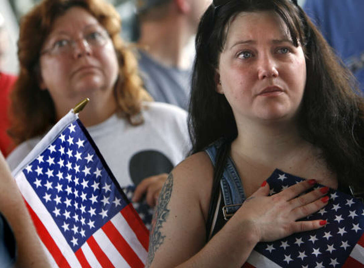 Melinda Cody, left, and Jodi Stafford listen during an anti-immigration rally that was moved to a parking lot in Morristown, Tenn., in late June after frustration with the police presence at the original site. Cody said she doesn't think the way Appalachia natives have reacted to illegal immigrants is unique.