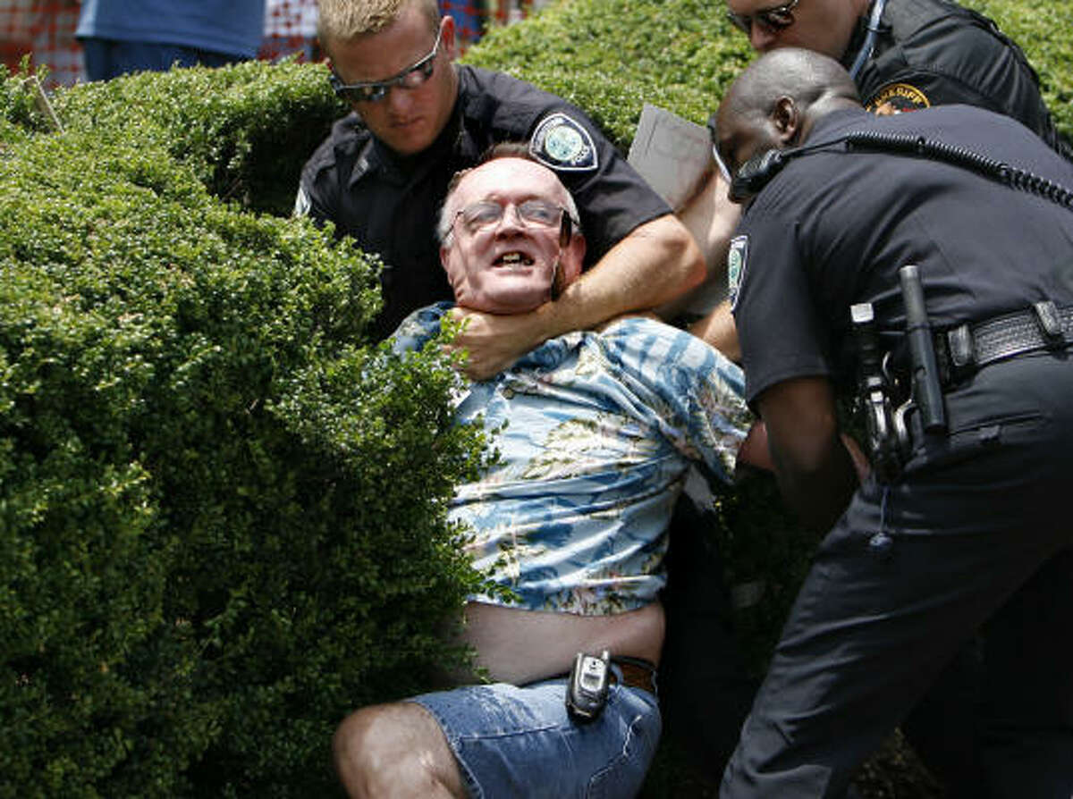 Ted Mitchell, 62, is arrested after refusing to give up the pole holding his American flag earlier at the original rally site in front of the Hamblen County Courthouse in Morristown, Tenn.
