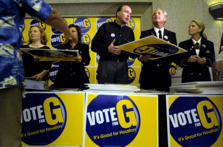 Continental Airlines Chairman and CEO Larry Kellner, center, helps pass out yard signs in support of Proposition G on Monday at the airline's downtown offices. Photo: Johnny Hanson, For The Chronicle