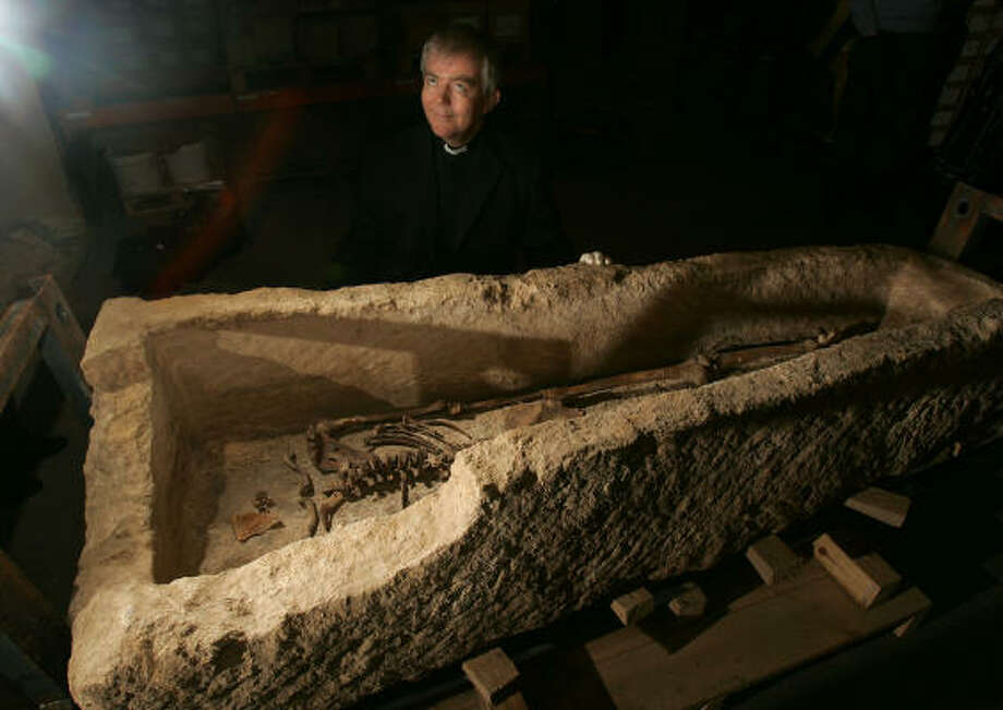 Vicar Nicholas Holtam stands by a Roman limestone sarcophagus containing a headless skeleton discovered by archaeologists during renovations at St. Martin-in-the-Fields church in London. The sarcophagus, which was made from a single piece of limestone, will go on display at the Museum of London. Photo: ALASTAIR GRANT, AP