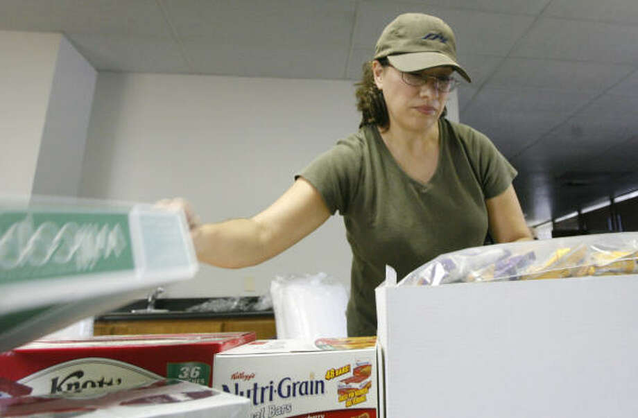 Sylvia Grice, Pfc. Kristian Menchaca's cousin, packs snacks to send to troops. Her co-workers have also helped in the effort. Photo: Billy Smith II, Chronicle