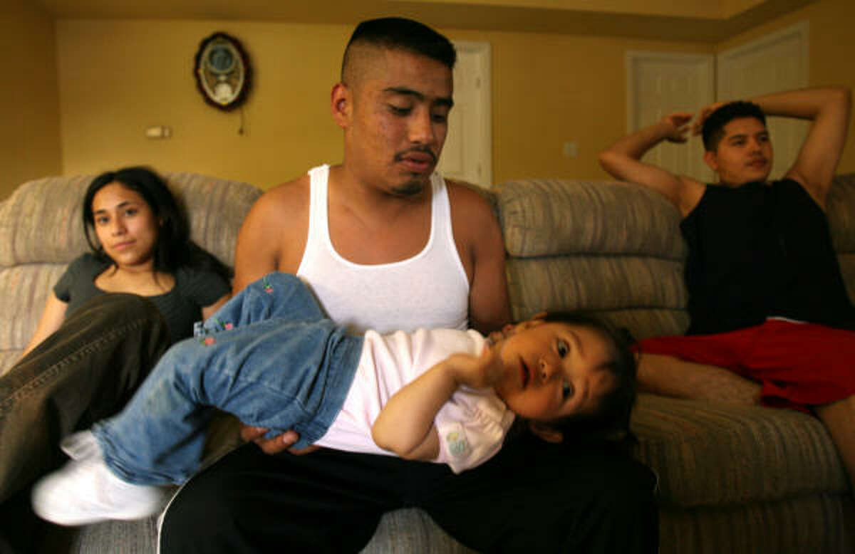 Israel Nuñez plays with his niece, Zurisaday Nuñez, as her mother, Erika Nuñez, 25, and father, Juan Madrigal, 22, kick back after a long day at work. Zurisaday's parents say their future in Morristown depends on whether the law gets tougher for undocumented immigrants.