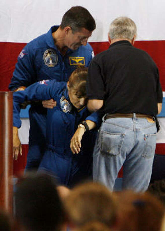 Astronaut Dan Burbank, left, and an unidentified man help Heide Stefanyshyn-Piper after she fainted a second time Friday on a stage at Ellington Field. Photo: KAREN WARREN, Chronicle