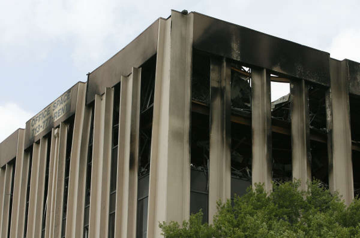 Bent columns can be seen at the office building where three people died in a fire March 28.
