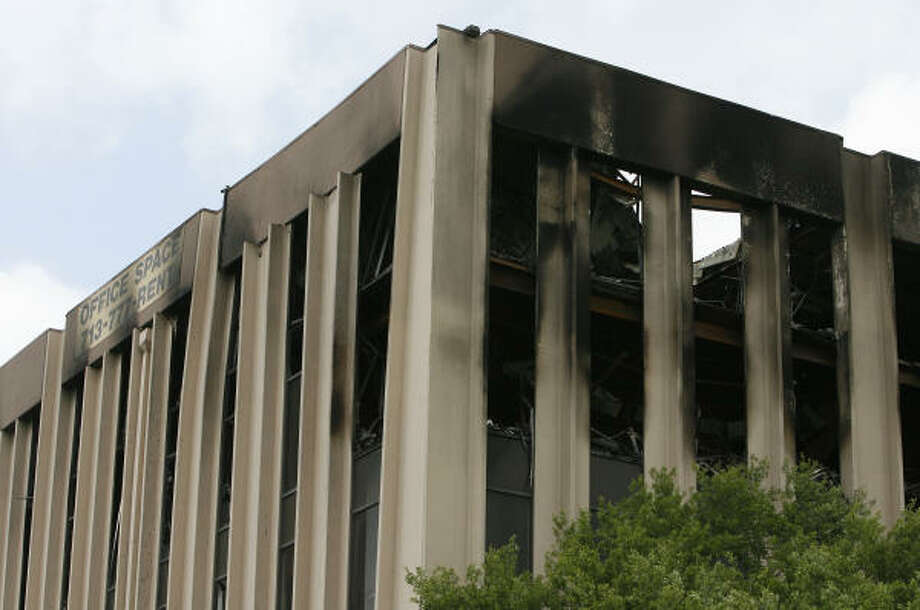 Bent columns can be seen at the office building where three people died in a fire March 28. Photo: James Nielsen, Chronicle