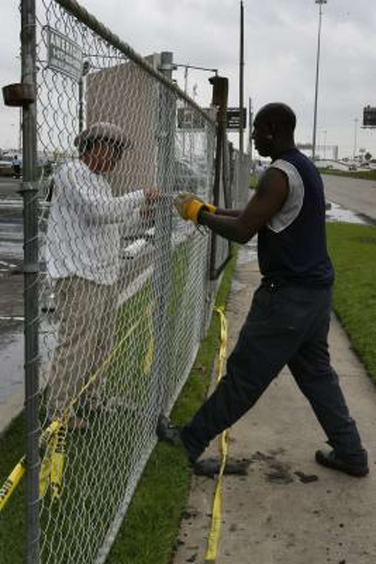 Jose Medina and Daryl Myers with American Fence Co. install a chain-link fence March 29 around the office building that burned in northeast Houston, killing three people March 28.