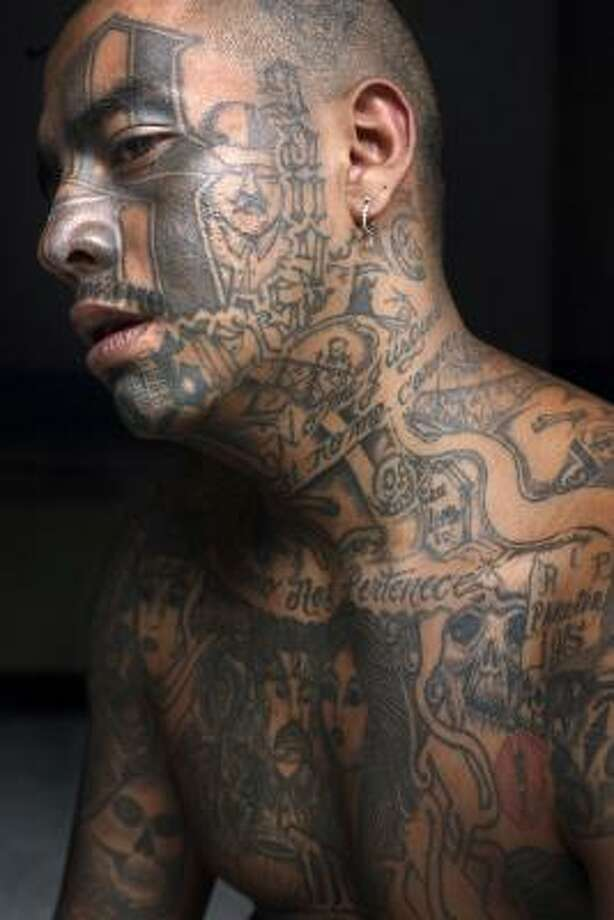 "A Mara gang member who identifies himself as ""Smoking,"" 25, poses for his portrait in prison in Chimaltenango, Guatemala, in this Oct. 19 file photo. After anti-gang laws were approved in Honduras and El Salvador, and a string of killings in Guatemala committed by neighbors and security forces, gang members have stopped tattooing themselves. Photo: Rodrigo Abd, AP"