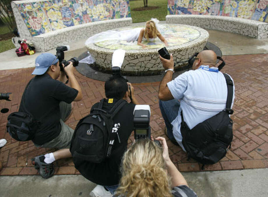 """Kimbie Lauderdale lies in a fountain in the Market Square area of downtown surrounded by photographers during the """"Trash the Dress"""" photo shoot in downtown Houston, Saturday, December 1, 2007. Photo: Karen Warren, Chronicle"""
