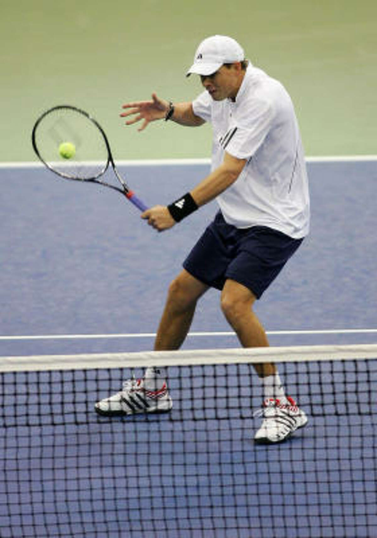 Bob Bryan of the U.S. volleys against Igor Andreev and Nikolay Davydenko of Russia during the second day of the Davis Cup Final at the Memorial Coliseum in Portland, Oregon.