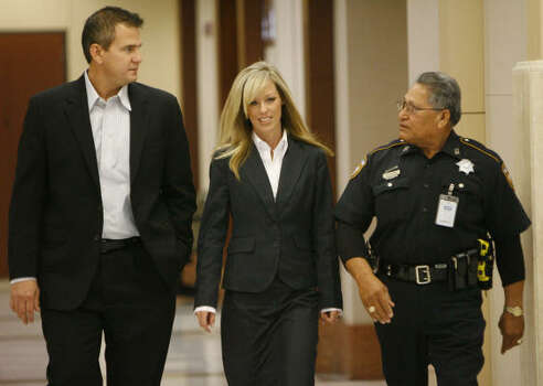 Heather Scott, wife of David Mark Temple, walks to the courtroom with Kevin Temple, David Temple's brother, left, and a court bailiff, Oct. 25. Photo: Melissa Phillip, Chronicle