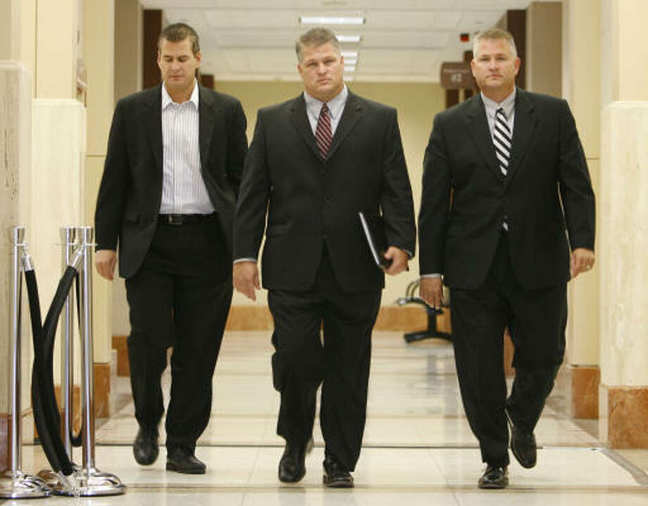 The Temple brothers, Kevin, from left, David and Darren, walk to court Oct. 24. Photo: Kevin Fujii, Chronicle