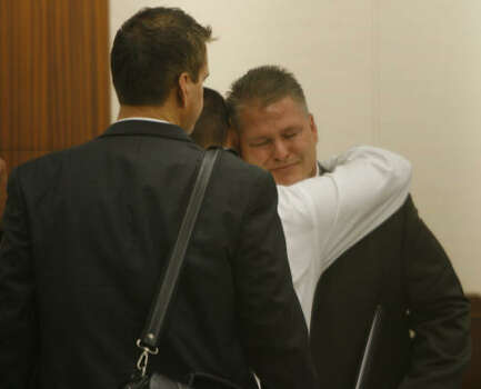 A supporter hugs David Temple after hearing the 911 call in his attorney's opening statement, Oct. 16. Photo: Kevin Fujii, Chronicle