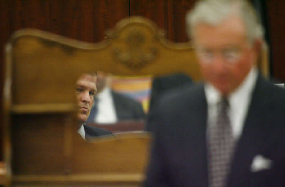 Defendant David Temple is reflected in a mirror on a hutch which is evidence in his trial as his lead defense counsel, Dick DeGuerin, walks by. Photo: Steve Ueckert, Chronicle