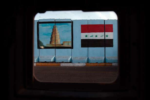 """An Iraqi flag and the spiral minaret of Samarra are painted on a concrete security """"blast wall"""" in Baghdad, Iraq."""
